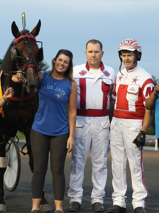 New Image Media |  Trainer Scott McEneny (center) — with driver Paul MacDonell after a win with trotter Stuck In My Spanks — is having a terrific year with young horses.
